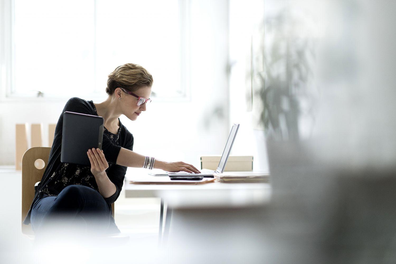 Eine Frau arbeitet im Büro mit Laptop und Tablet.