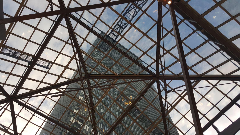 Stahl- und Glasdach; Im Hintergrund ist ein Hochhaus zu erkennen