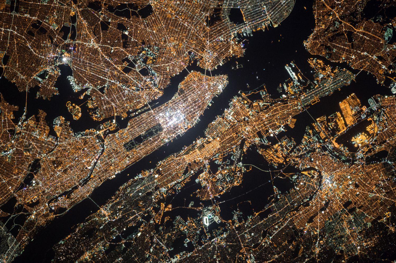 Großstadt im Lichtermeer aus der Vogelperspektive. Kritische Infrastrukturen müssen besonders abgesichert sind.