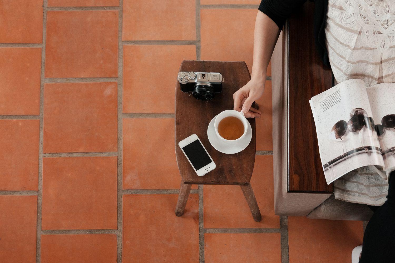 Zeitungsleserin; Teetasse und Smartphone befinden sich neben ihr auf einem Beistelltisch. Thema: Finanzbranche