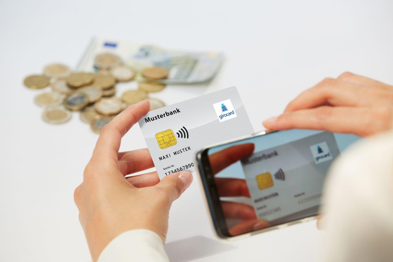 Person, die eine Bankkarte und Smartphone in der Hand hält, im Hintergrund Bargeld.