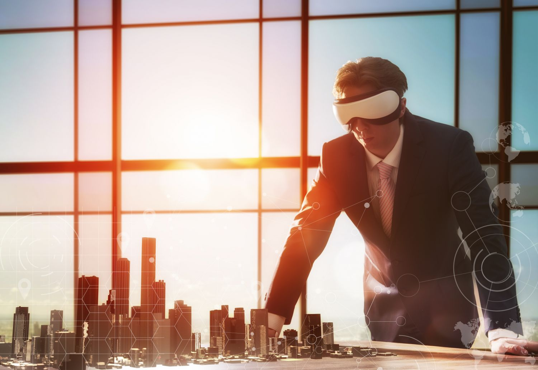 Person mit VR-Brille vor einer Skyline im Sonnenaufgang