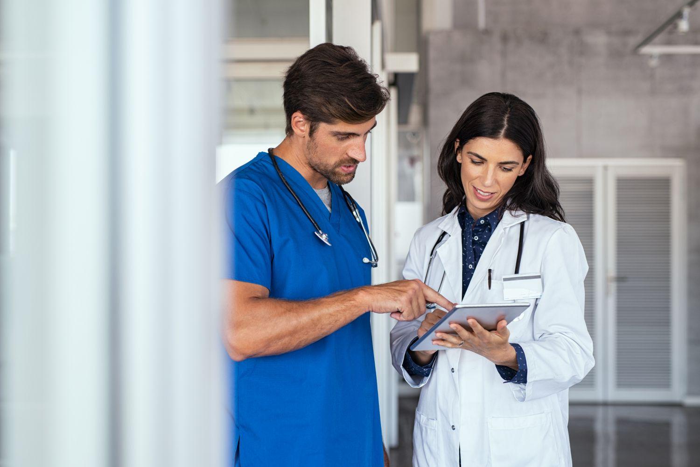Krankenpfleger und Ärztin stehen zusammen und diskutieren Patientendaten mit einem Tablet.